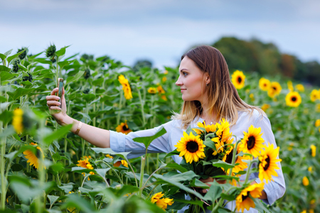 Beautiful young woman making selfie with smartphone on sunflower field with bouquet flowers. Happy girl on summer sunset day.