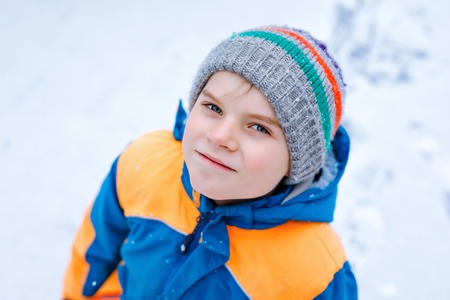 Portrait of little school kid boy in colorful clothes playing outdoors during snowfall. Active leisure with children in winter on cold snowy days. Happy healthy child having fun and playing with snow.