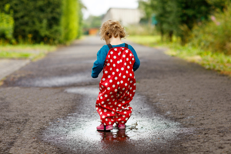 Close-up of little toddler girl wearing rain boots and trousers and walking during sleet, rain on cold day. Baby child in colorful fashion casual clothes jumping in a puddle Foto de archivo - 117394925