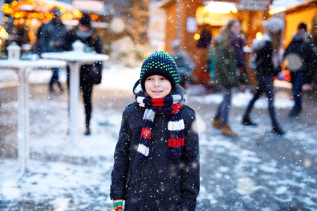 Little cute kid boy having fun on German Christmas market. Happy child on traditional family market in Germany, Laughing boy in colorful winter clothes 免版税图像