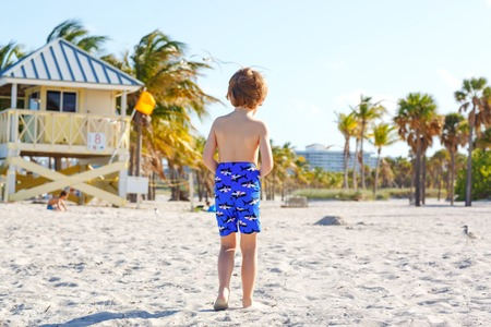 Blond little kid boy having fun on Miami beach, Key Biscayne. Happy healthy cute child playing with sand and running near ocean. Palms, security house and white sand