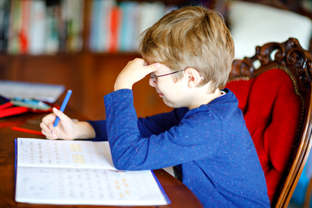 Portrait of frustrated crying sad school kid boy at home making homework. Little child writing with colorful pencils, indoors. Elementary school and education Stok Fotoğraf - 117394928