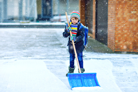 Little school kid boy of elementary class cleaning snow with shovel before going to school. Happy child having fun with first snow. Student with backpack or satchel in colorful winter clothes.