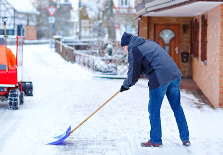 Man with snow shovel cleans sidewalks in winter during snowfall. Winter time in Europe. Young man in warm winter clothes. Snow and weather chaos in Germany. Snowstorm and heavy snowing. Schneechaos