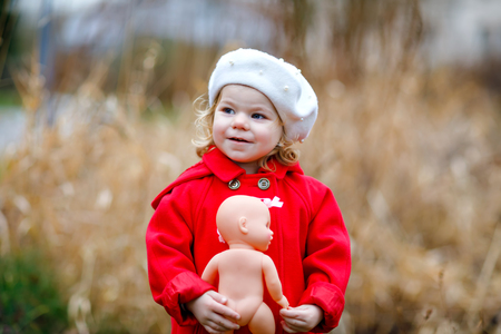 371958f758a Outdoor portrait of little cute toddler girl in red coat and white fashion  hat barret with