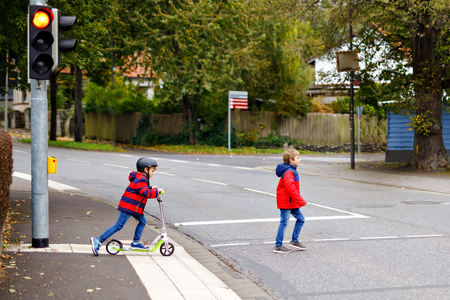 Two little schoolkids boys running and driving on scooter on autumn day. Happy children in colorful clothes and city traffic crossing pedestrian crosswalk with traffic lights. Archivio Fotografico - 117395932