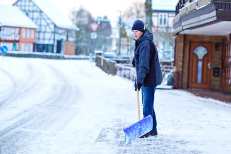 Man with snow shovel cleans sidewalks in winter during snowfall. Winter time in Europe. Young man in warm winter clothes. Snow and weather chaos in Germany. Snowstorm and heavy snowing. Schneechaos Foto de archivo - 117396061