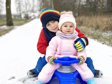 Little kid boy and cute toddler girl sitting together on sledge. Siblings, brother and baby sister enjoying sleigh ride during snowfall. Children sledding on snow. Active fun for family vacation 스톡 콘텐츠