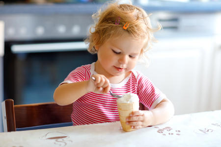 Adorable baby girl eating from spoon sweet ice cream in waffle cone. food, child, feeding and development concept. Cute toddler, daughter with spoon sitting in highchair and learning eat by itself