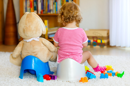 Closeup of cute little 12 months old toddler baby girl child sitting on potty. Kid playing with big plush soft toy. Toilet training concept. Baby learning, development steps Stock Photo