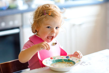 Adorable baby girl eating from spoon vegetable noodle soup. food, child, feeding and development concept. Cute toddler child, daughter with spoon sitting in highchair and learning to eat by itself