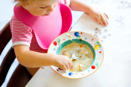 Close-up baby girl eating from spoon vegetable noodle soup. food, child, feeding and development concept. closeup of toddler, daughter with spoon sitting in highchair and learning to eat by itself 写真素材