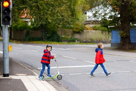 Two little schoolkids boys running and driving on scooter on autumn day. Happy children in colorful clothes and city traffic crossing pedestrian crosswalk with traffic lights. Stock Photo