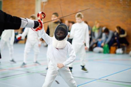 Petit garçon d'escrime sur une compétition de clôture. Enfant en uniforme d'escrimeur blanc avec masque et sabre. Formation active d'enfant avec l'enseignant et les enfants. Sports et loisirs sains. Banque d'images