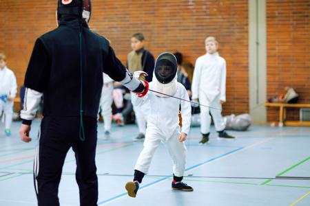 Little kid boy fencing on a fence competition. Child in white fencer uniform with mask and sabre. Active kid training with teacher and children. Healthy sports and leisure. Standard-Bild