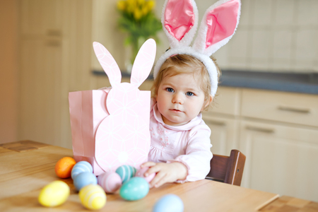 Cute little toddler girl wearing Easter bunny ears playing with colored pastel eggs. Happy baby child unpacking gifts. Adorable healthy smiling kid in pink clothes enjoying family holiday Stockfoto