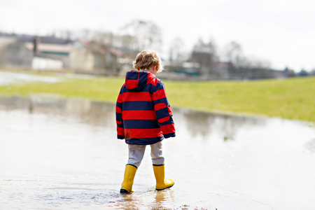 Little kid boy wearing yellow rain boots and walking and jumping into puddle on warm sunny spring day. Happy child in colorful fashion casual rain clothes having fun and playing outdoors.