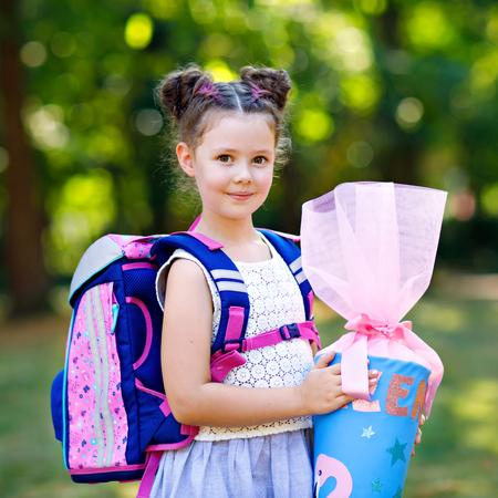 Glückliches kleines Mädchen mit Rucksack oder Schulranzen und großer Schultasche oder Kegel traditionell in Deutschland für den ersten Schultag. Gesundes entzückendes Kind im Freien, im grünen Park.