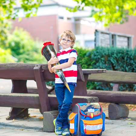 Happy little kid boy with glasses and backpack or satchel on his first day to school . Child outdoors on warm sunny day, Back to school concept. Kid with traditional schoolbag in German Schultuete.