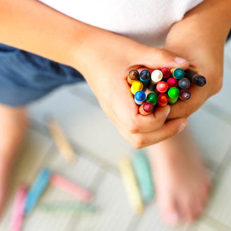 Close-up of childs hands with lots of colorful wax crayons pencils. Kid preparing school and nursery equipment and student stuff. Back to school. Education, school, learning concept.. Stockfoto