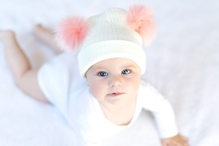 Cute adorable baby child with warm white and pink hat with cute bobbles. Happy baby girl learning crawl and looking at the camera. Close-up for xmas holiday and family concept..