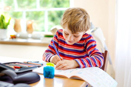 Happy smiling little kid boy at home making homework at the morning before the school starts. Little child doing excercise, indoors. Elementary school and education: Boy drawing geometric figures