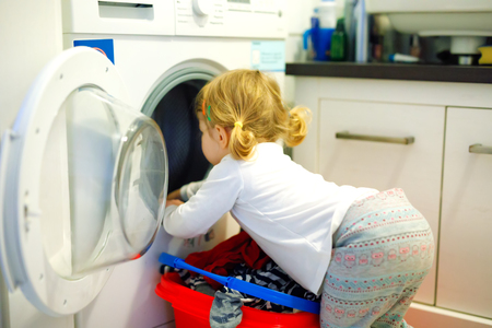 Cute baby toddler girl taking clean clothes from the washing machine. Adorable child, healthy daughter helping mom with laundry. Stockfoto