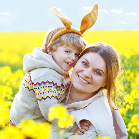 Little child and his mother in Easter bunny ears having fun, celebrating traditional Easter holiday. Kid toddler boy and mum, woman In yellow rape field, outdoors. Family together, love, happiness.