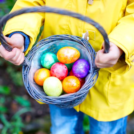Nahaufnahme der Hände des kleinen Kindes mit bunten Ostereiern im Korb. Kind macht eine Eiersuche. Kind sucht und findet bunte Eier im heimischen Garten. Alte christliche und katholische Tradition.
