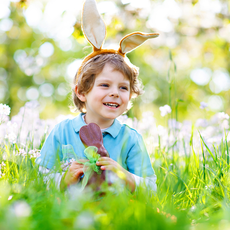 Cute little kid boy with Easter bunny ears celebrating traditional feast. Happy child eating chocolate rabbit fugure on warm sunny day. Family, holiday, spring concept. Toddler sitting between flowers Stock Photo
