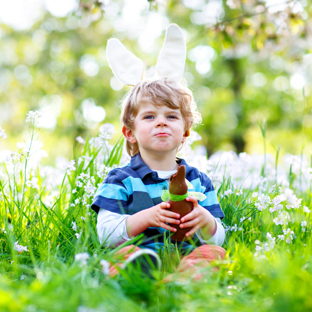 Cute little kid boy with Easter bunny ears celebrating traditional feast. Happy child eating chocolate rabbit fugure on warm sunny day. Family, holiday, spring concept. Stock Photo