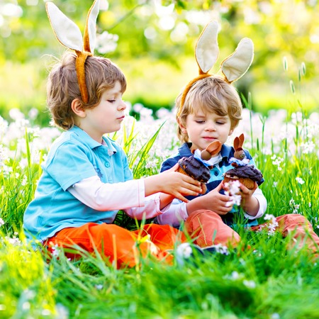 Two little kids boys and friends in Easter bunny ears during traditional egg hunt in spring garden, outdoors. Siblings eating chocolate cake, muffin and cupcake. Old christian and catholoc tradition. 写真素材