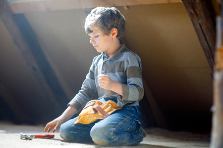 Little kid boy helping with toy tools on construction site. Funny child of 6 years having fun on building new family home. Kid with nails and hammer helping father to renovate old house. Stock Photo - 118152130