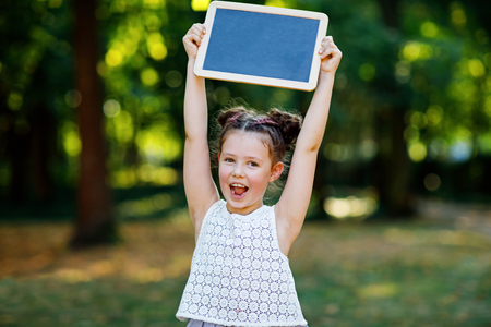 Happy little kid girl holding empty chalk desk in hands. Schoolkid on first day of elementary class. Healthy adorable child outdoors, in green park. Copyspace on desk
