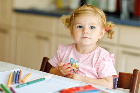 Cute adorable baby girl learning painting with pencils. Little toddler child drawing at home, using colorful felt tip pens. Healthy happy daughter experimenting with colors at home or nursery.