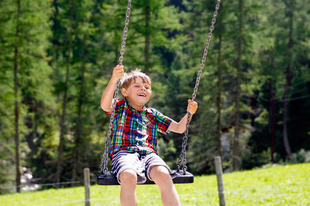 Funny kid boy having fun with chain swing on outdoor playground while being wet splashed with water. child swinging on summer day. Active leisure with kids. Happy crying boy with rain drops on face.