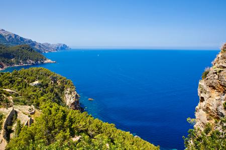 Island scenery, seascape of Mallorca Spain. Idyllic coastline of Majorca, Mediterranean Sea on sunny day. Turquoise water and green hills of Serra de Tramuntana.