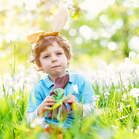 Cute little kid boy with Easter bunny ears celebrating traditional feast. Happy child eating chocolate rabbit fugure on warm sunny day. Family, holiday, spring concept. Toddler sitting on grass Stock Photo