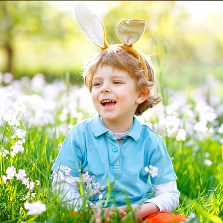 Cute little kid boy with Easter bunny ears celebrating traditional feast. Happy child smiling on warm sunny day. Family, holiday, spring concept. Toddler sitting on grass between flowers. Stock Photo