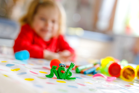 Adorable cute little toddler girl with colorful clay. Healthy baby playing and creating toys from play dough. Small kid molding modeling clay and learning. Focus on frog made with clay Imagens