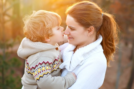 Mother and little son in park or forest, outdoors. Hugging and having fun together. Happy toddler boy and young mum, kid and woman playing