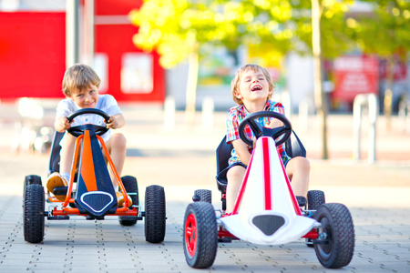 Two active little kid boys driving pedal race car in summer garden, outdoors. Children, best friends racing with fast speed and having fun. Twins making competition. 免版税图像