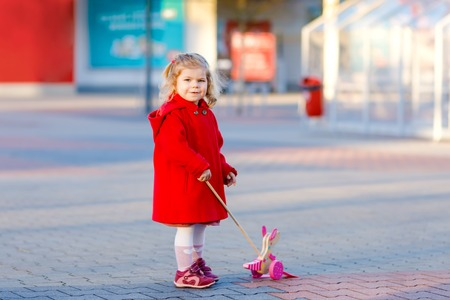 Outdoor portrait of little cute toddler girl in red coat aon spring sunny day with push wooden toy. Healthy happy baby child walking in the city. Fashion stylish clothes for kids.