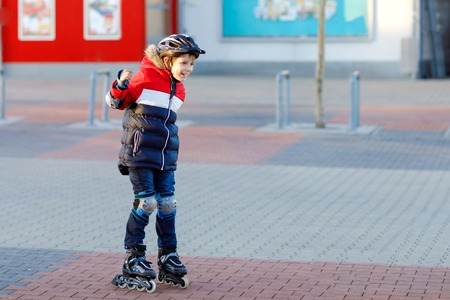 Cute school kid boy skating with rollers in the city. Happy healthy child in protection safety clothes skating with rollers. Active schoolboy making sports and learning to skate on inline skater.