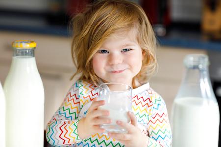 Aanbiddelijk peutermeisje dat koemelk drinkt voor het ontbijt. Schattige baby dochter met veel flessen. Gezond kind met melk als bron van gezondheidscalcium. Kind thuis of kinderdagverblijf in de ochtend.