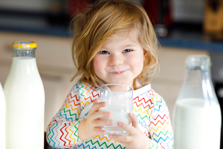 Adorable toddler girl drinking cow milk for breakfast. Cute baby daughter with lots of bottles. Healthy child having milk as health calcium source. Kid at home or nursery in the morning. Stock Photo