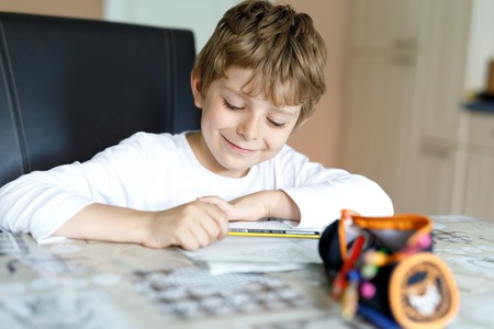 Tired little kid boy at home making homework at the morning before the school starts. Little child doing excercise, indoors. Elementary school and education. Stok Fotoğraf - 119615851