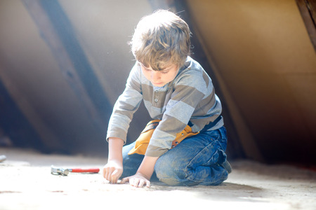 Little kid boy helping with toy tools on construction site. Funny child of 6 years having fun on building new family home. Kid with nails and hammer helping father to renovate old house. Stock Photo - 119615856
