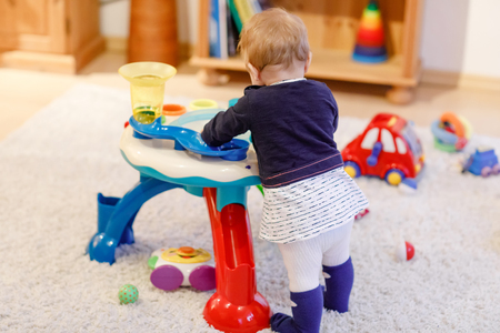 Adorable cute beautiful little baby girl playing with educational sorter toys at home or nursery. Healthy happy toddler child learning sorting colors and forms Reklamní fotografie