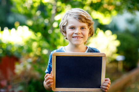 Happy little kid boy with chalk desk in hands. Healthy adorable child outdoors Empty desk for copyspace holding by beautiful schoolkid Reklamní fotografie